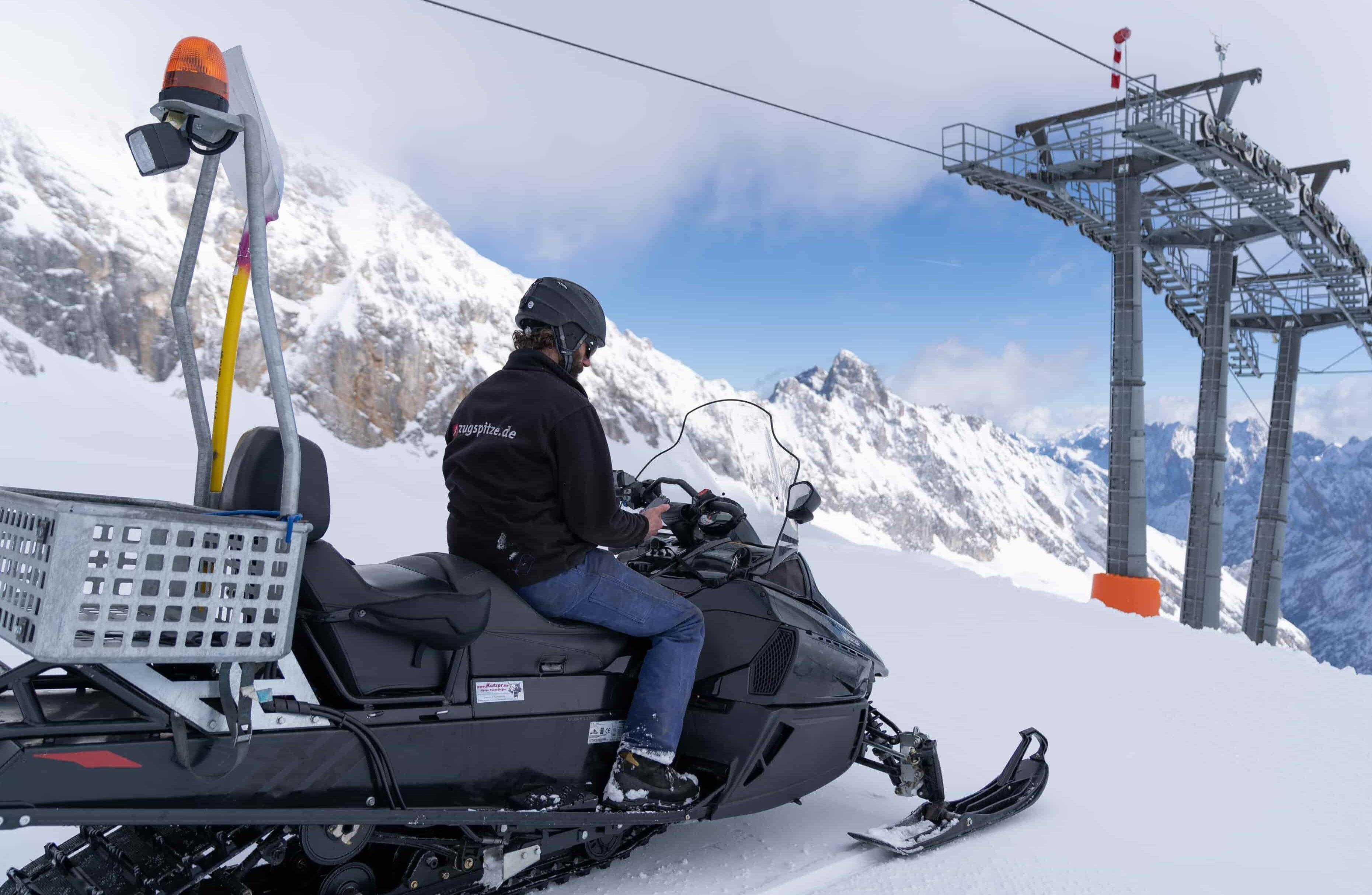 Mitarbeiter auf Skidoo im Skigebiet mit Handy in der Hand