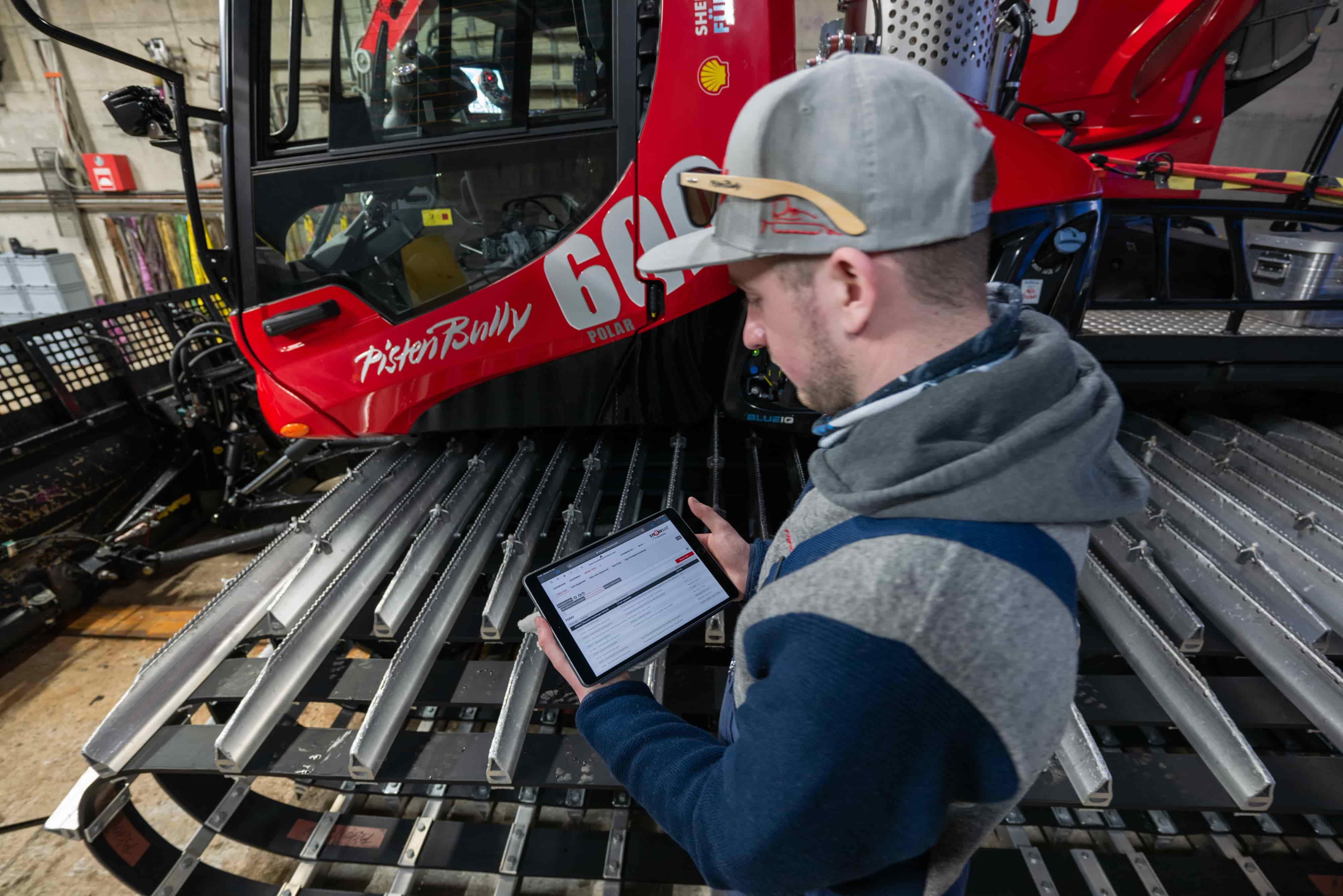 Werkstatt-Mitarbeiter mit SNOWsat Maintain auf dem Tablet vor einem PistenBully