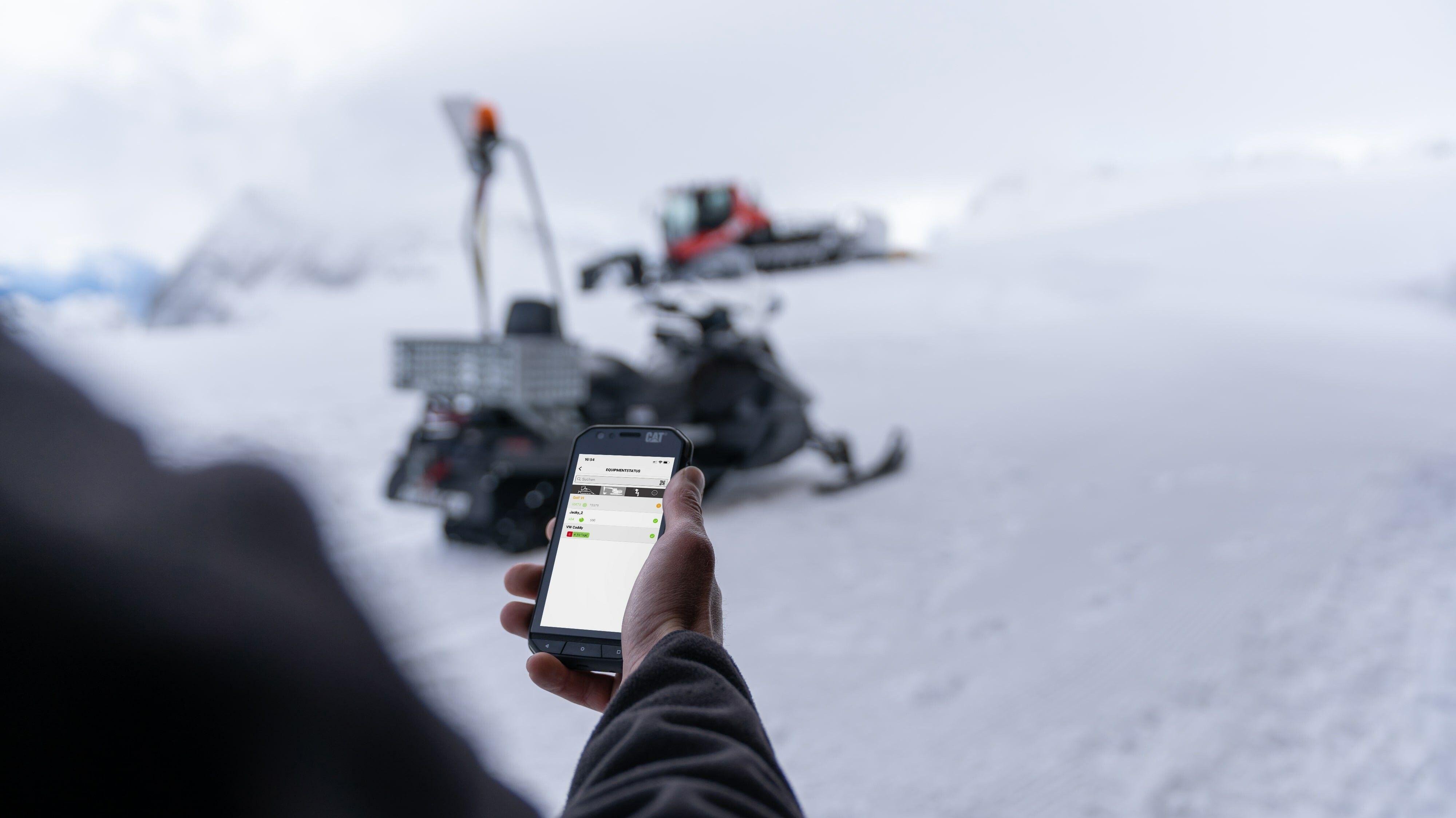 Hand mit Smartphone und SNOWsat App, im Hintergrund Skidoo und PistenBully