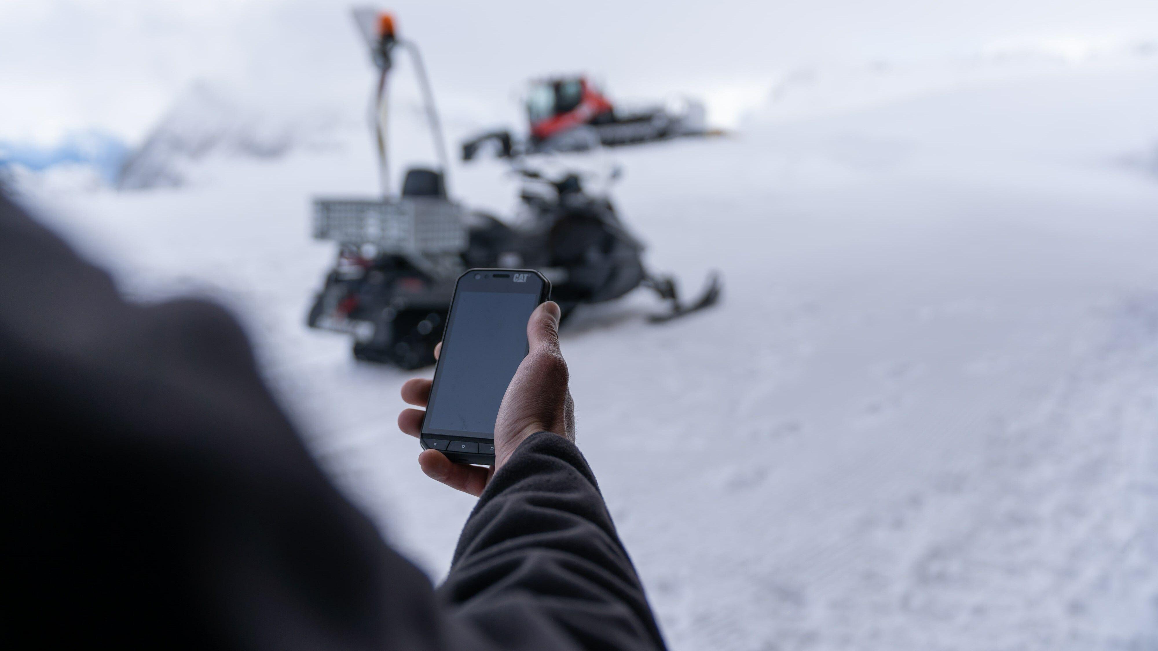 Mitarbeiter im Skigebiet mit Handy in der Hand